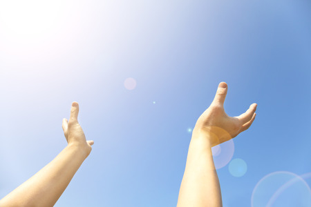 recieve: Two hands with the opened palms last upwards to the blue sky Stock Photo