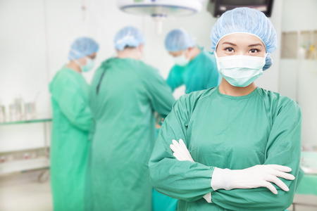 physicals: confident female surgeons  crossed hands with  teams   Stock Photo