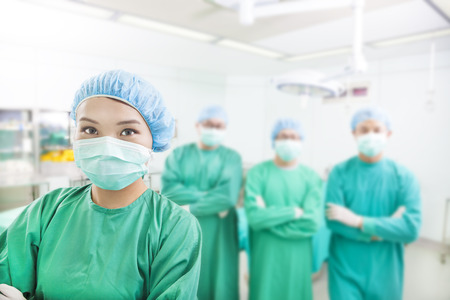 cosmetic surgery: Smiling surgeon posing with aesthetic medicine teams Stock Photo