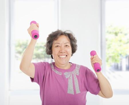 dumbell: happy senior woman working out with dumbbells at home