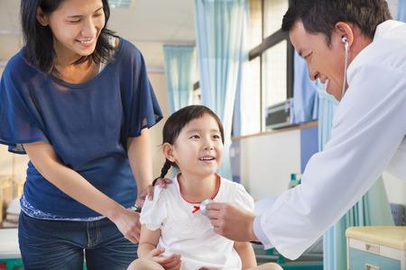 medical doctors: pediatrician examining little girl , her mother beside her