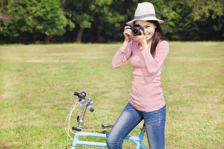 folding camera: female photographer holding camera and sitting bike Stock Photo