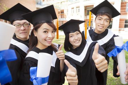 estudiantes universitarios: Grupo de estudiantes que se gradúan que sostiene el diploma y el pulgar arriba