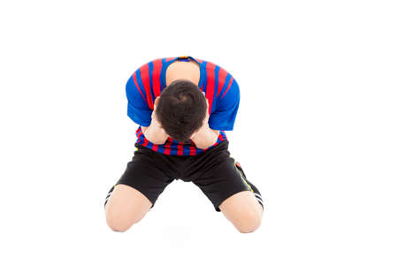 kneel down: agitated soccer player kneel down and  cover his face to cry