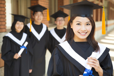 college campus: beautiful  college graduate holding diploma with classmates