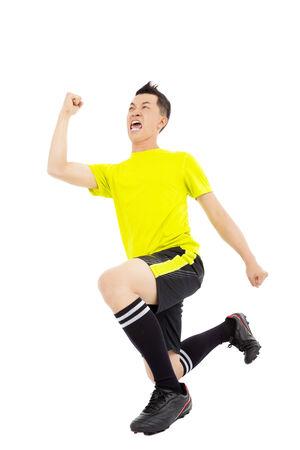 arrodillarse: Jugador de fútbol joven emocionado la mano levantada y arrodillándose
