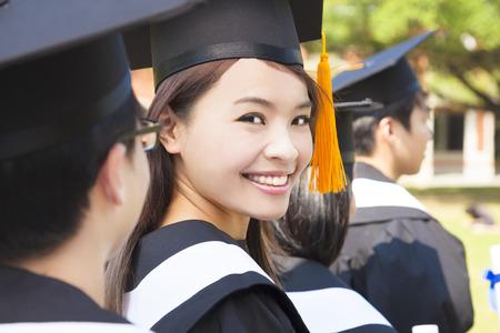 Mujer que se coloca hacia fuera de un grupo de graduación sonriendo