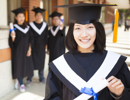 pretty  female college graduate holding diploma with classmates photo