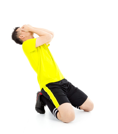 indoor soccer: Upset  or excited soccer player kneeling down Stock Photo