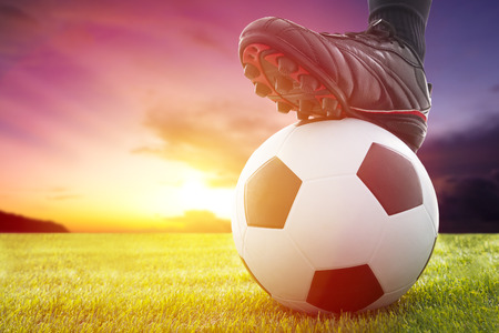 soccer ball on grass: Football or soccer ball at the kickoff of a game with sunset Stock Photo
