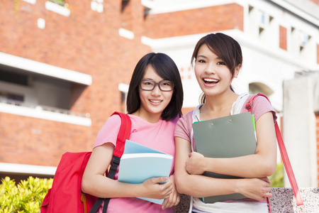two smiling students holding books  at compus