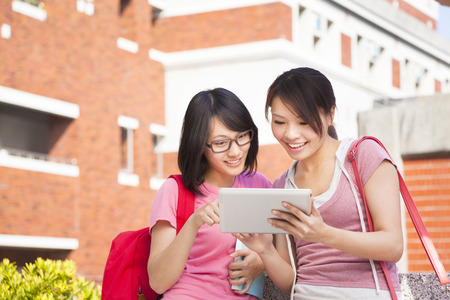 two students using a tablet to discuss homework photo