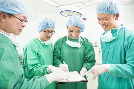 sufferer: happy Surgeons discussing success operating procedure Stock Photo