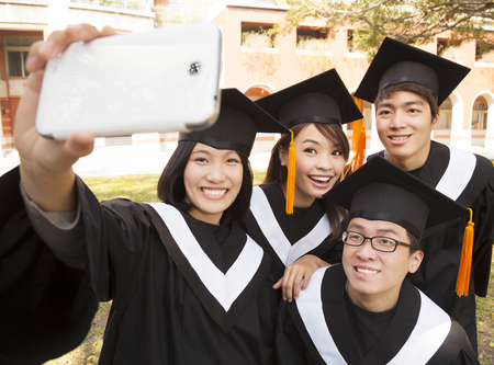 graduate hat: group of graduates  taking picture with cell phone