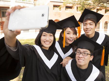 grupo de graduados que toman el cuadro con el teléfono celular