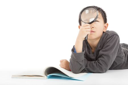 happy kid is holding magnifying glass to explore  photo