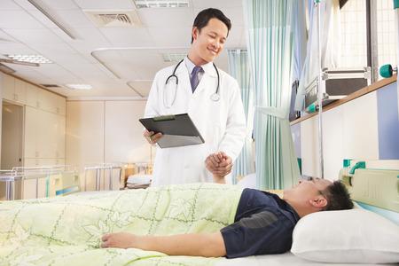 doctor sonriente sosteniendo la mano del paciente para animarle
