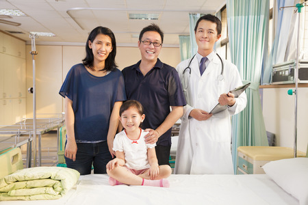 asian hospital: happy family and pediatrician standing in the ward