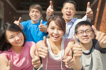 Group of happy students with thumbs up photo