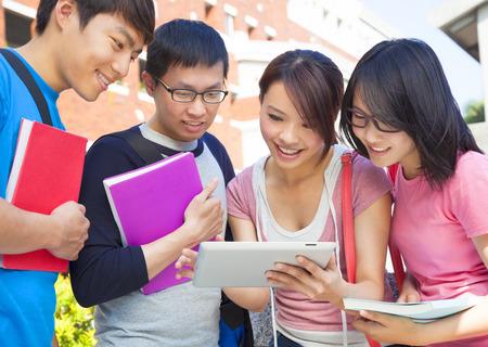 educacion universitaria: grupo de estudiantes discutiendo la tarea mediante el uso de la tableta