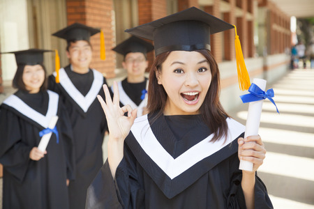 happy college graduate holding diploma  and make a gesture photo