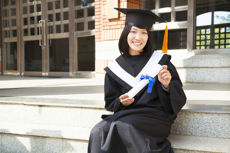 Asian college student holding a diploma at campus photo