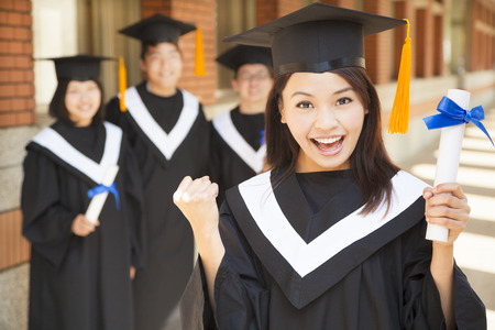 happy college graduate holding diploma  and make a fist