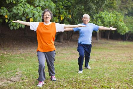 senior asian: Active senior couple in the park doing gymnastics