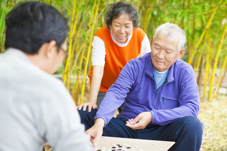 senior asian: seniors play traditional chinese board game Go