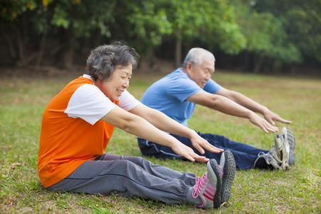 in action: Happy elderly seniors couple working out in park Stock Photo