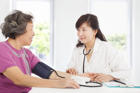 examining: doctor measuring blood pressure of senior woman at home