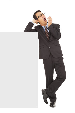 yawing: businessman yawning and standing  with blank board