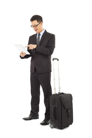 Young businessman using a tablet  with briefcase  photo