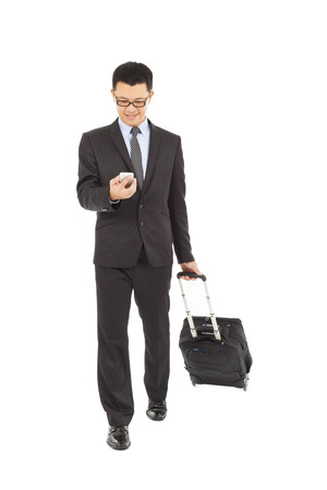 businessman walking and using phone  with briefcase  photo