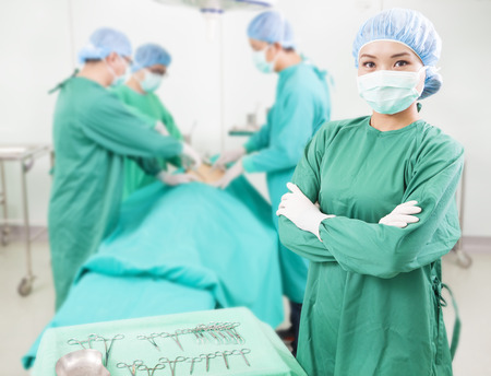 medical procedure: surgeon standing in front of a colleague in a surgical room