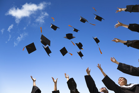 egresado: Los estudiantes que lanzan los sombreros de graduaci�n en el aire la celebraci�n de Foto de archivo