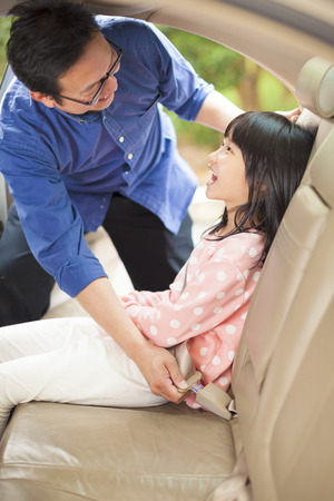 vehicle seat: father help daughter to fasten a seat belt