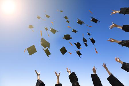 graduacion de universidad: felices jóvenes graduados tirando sombreros