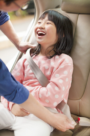 seat belt: father take care daughter to fasten a seat belt