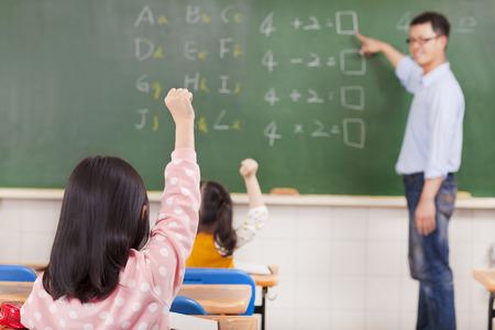 alumnos estudiando: Los estudiantes de primaria que levanta las manos