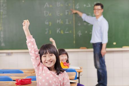 asian teacher: pupils raising hands during the lesson with teacher