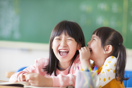people laughing: Laughing little girls sharing secrets in class