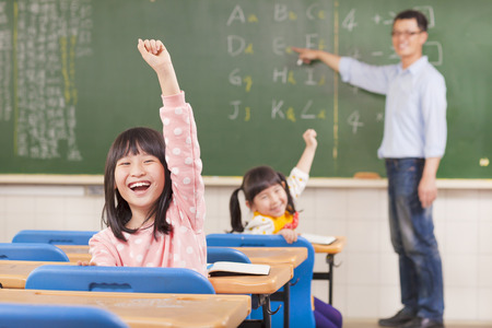 asian pupils raising hands during the lesson  photo