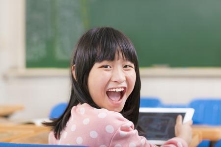 happy little schoolgirl holding digital tablet at desk photo