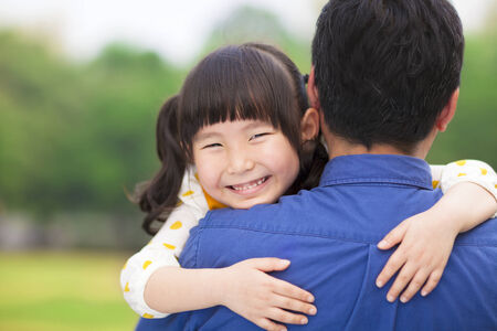 father daughter: happy little girl hugging embracing her father Stock Photo