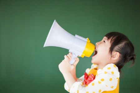 announce: Happy child  using a megaphone with blackboard