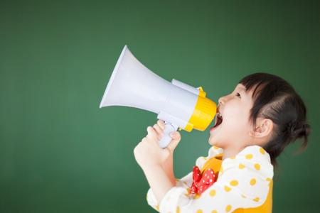 megafono: Niño feliz usando un megáfono con la pizarra Foto de archivo