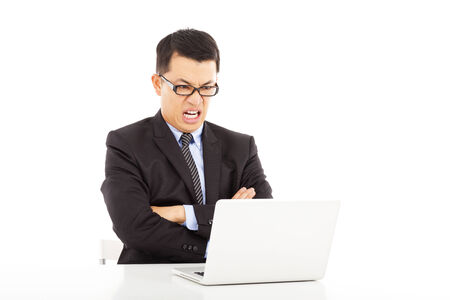 angry businessman look at laptop and cross arms photo