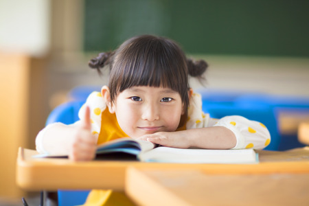 smiling kid lie prone on a desk and thumb up photo