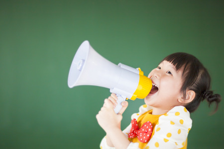 Schattig kind met behulp van een megafoon in een klaslokaal Stockfoto - 26773639